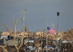 A flag files at half staff over devastated Joplin High School next to a portable tornado siren in Joplin, Mo. Thursday, May 26, 2011. (AP Photo/Charlie Riedel)