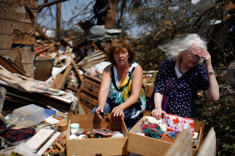 Two women sorting belongings at a tornado-damaged home