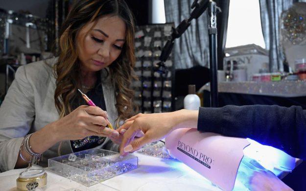 a nail salon worker applies a manicure