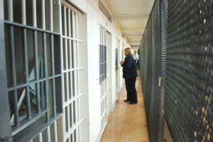 A prison warden in a dark suit in a cellblock hallway.